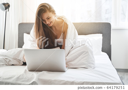 Woman wrapped in the blanket sitting in bed 64179251