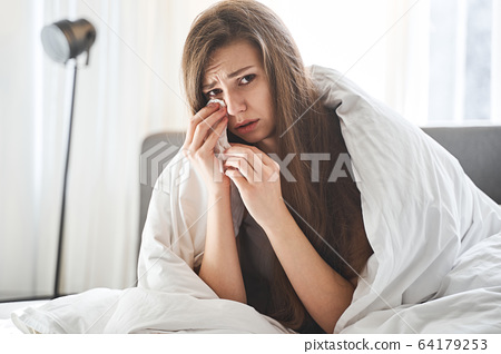 Dispirited ill woman holding a paper tissue 64179253