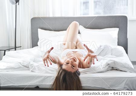 Joyous girl lying on a duvet in a bedroom 64179273