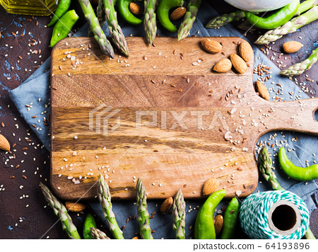 Wooden chopping board with asparagus, nuts, salt 64193896