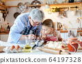 Family is cooking in cozy kitchen at home. Grandmother and child are making italian food and meal. 64197328