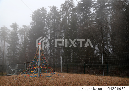 Children's rides stretched out by conifers next to a thick Czech rest area 64206083