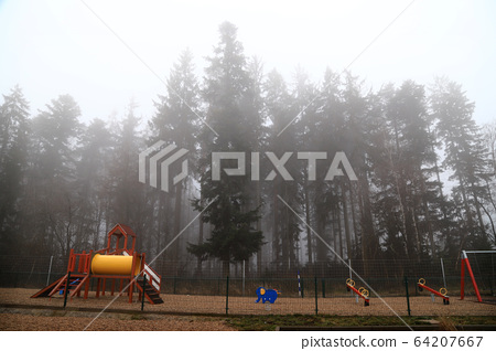Children playground on a foggy highway rest area 64207667
