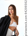 girl in white with a black jacket on a light 64209302