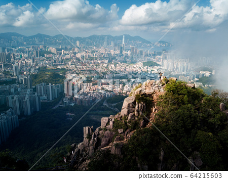 Man standing on the Lion rock above Hong Kong 64215603