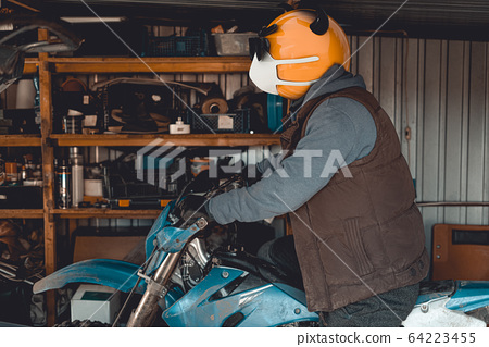Emoji motocross rider with fancy black nerd sunglasses on his motorcycle inside of garage . Emoji with mask protecting against coronavirus  Covid 19. 3D rendering and photography collage. 64223455