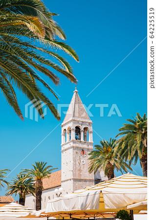 Trogir seaside street with tropical palm trees at summer in Trogir, Croatia 64225519