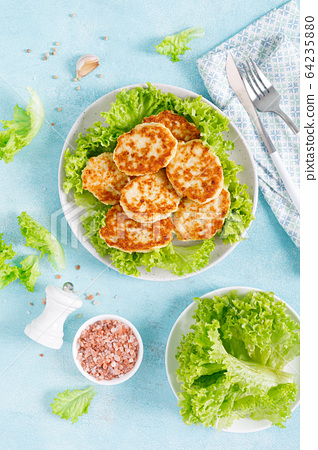 Chicken cutlets with fresh lettuce salad on plate 64235880