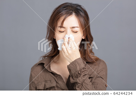 Sick young woman  blowing her nose 64244234