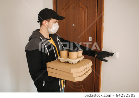 Man delivery pizza and coffe to customer in mask and gloves. Coronavirus theme. Man ring the doorbell 64252585