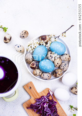 Process of painting Easter eggs in blue 64253155