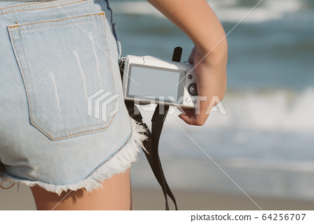 Close up hand of woman tourist  holding camera on nature background. Female with camera over beach; freedom, travel concept; Free from copy space.  64256707