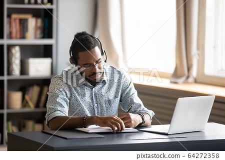 Concentrated biracial guy listening to favorite music while planning workday. 64272358