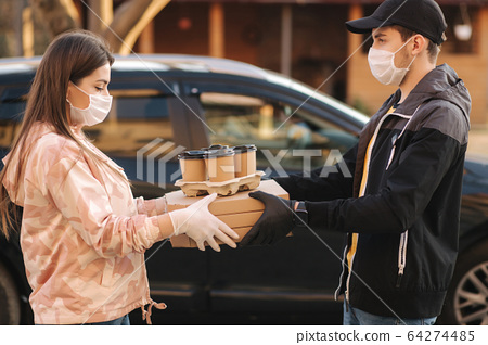 Young woman in protective mask and medical mask take order from delivery boy outside. Food delivery in quarantine. Courier bring Pizza and coffee for customer 64274485