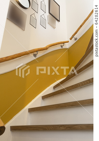 wooden stair with yellow wall and blank frames hanging, retro modern design 64282614