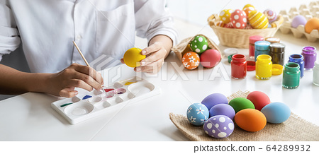 Happy Asian woman painting eggs for Eastertime at home. Family preparing for Easter. 64289932