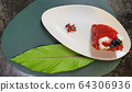 strawberry cake on a white plate and big leaf 64306936