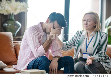 Young man in a pink shirt feeling desperate andunhappy 64314174