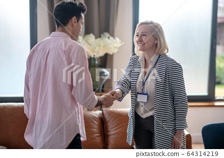 Blond psychologist greeting her young male patient in her office and smiling 64314219