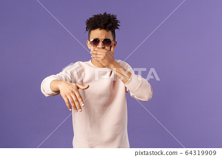 Waist-up portrait of cool and sassy, young carefree guy with dreads and sunglasses, cover mouth to beatbox, waving hand in rhythm music, singing rap or attend hip-hop party, purple background 64319909