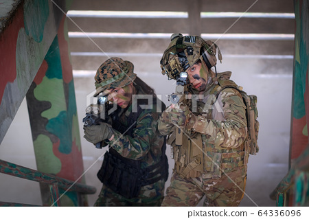 Two of woman soldiers hold gun and walk through step and go up to top of defensive base 64336096
