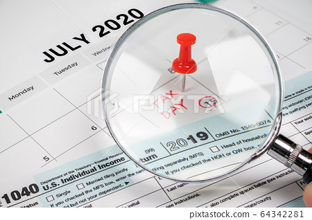The tax day was extended to July 15th because of Covid-19. July calendar showing 1040 return form and tax day. 64342281