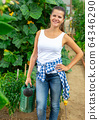 Woman posing during watering seedlings with watering pot 64346290