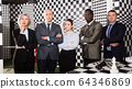 Businesspeople solving conundrum together near chessboard 64346869