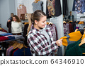 Woman choosing cardigan in clothing shop 64346910
