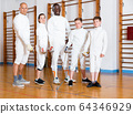 Group portrait of young fencers with coaches holding rapiers in training room 64346929