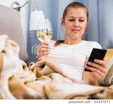 female with wine in glass using mobile phone 64347871