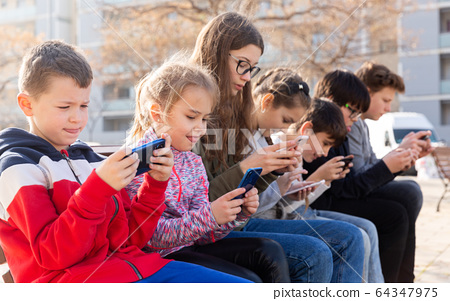 Group of children communicate using smartphones in the playground 64347975