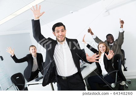 Excited businessman with happy team 64348260