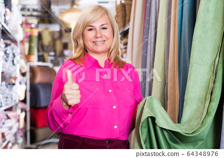 Woman seller showing curtain and holding thumb up 64348976