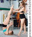 Sporty young woman exercising pole dance moves with trainer in fitness studio 64349264