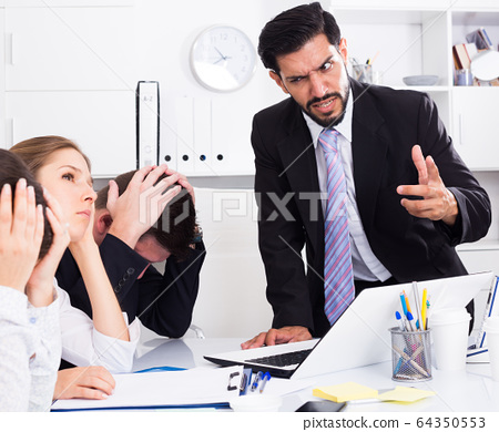Outraged manager with colleagues at meeting 64350553