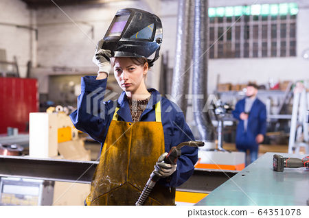 Young woman using welder for construction work 64351078