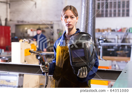 Young woman using welder for construction work 64351080