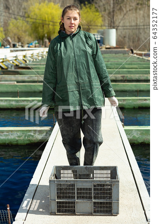 Female farm worker with crate of trout 64352177