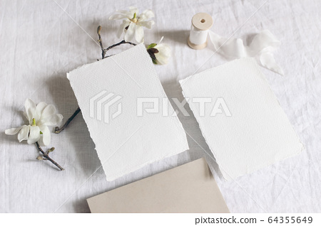 Wedding stationery set. Mock-up scene with blank paper greeting cards, envelope on linen tablecloth background. White magnolia stellata tree branches and ribbon. Feminine still life, flat lay, top. 64355649