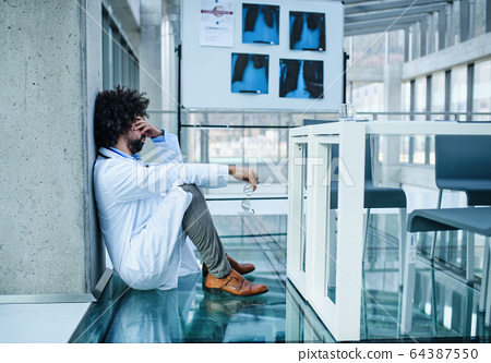 Worried and tired doctor in hospital, corona virus concept. 64387550