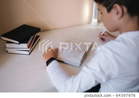 Young boy sitting at desk read the book and write down in notebook. Study at home during quarantine 64397976