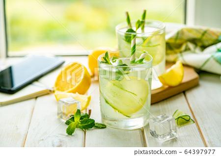 Summer lemonade in glasses in front of window 64397977