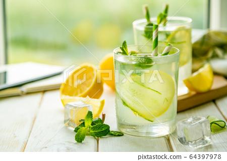 Summer lemonade in glasses in front of window 64397978