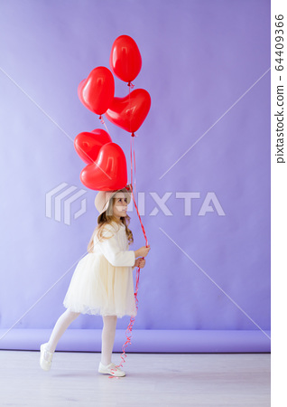 Little girl with red air in the shape of a heart 64409366
