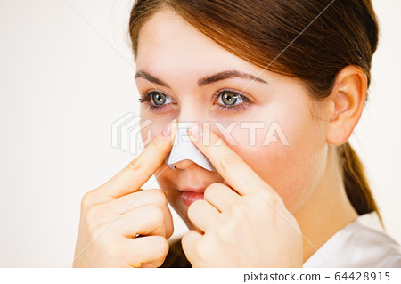 Woman applying pore strips on nose 64428915