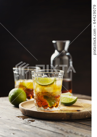 Strong golden rum with lime and ice 64429079