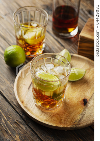 Strong golden rum with lime and ice 64429081
