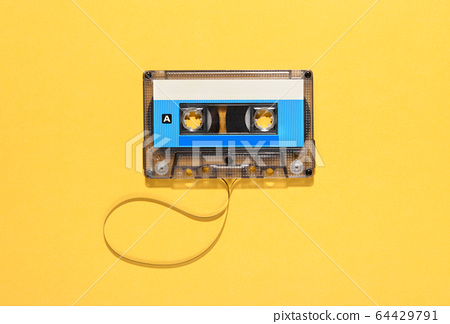 Vintage audio cassette with unwound tape spool over yellow with copy space viewed as a flat lay still life 64429791
