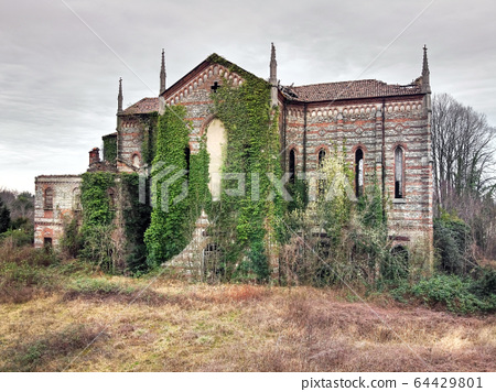 Old abandoned stone church overgrown with weeds 64429801